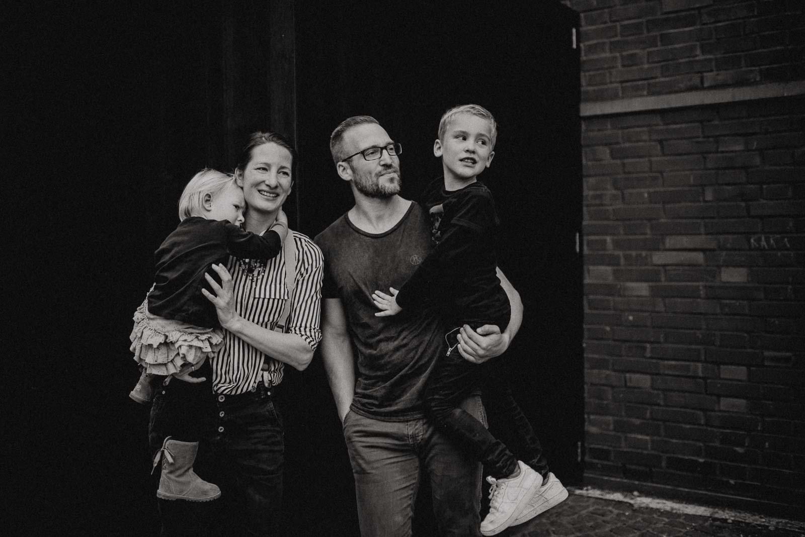 Vierköpfige Familie vor schwarzem Hintergrund bei Familienshooting