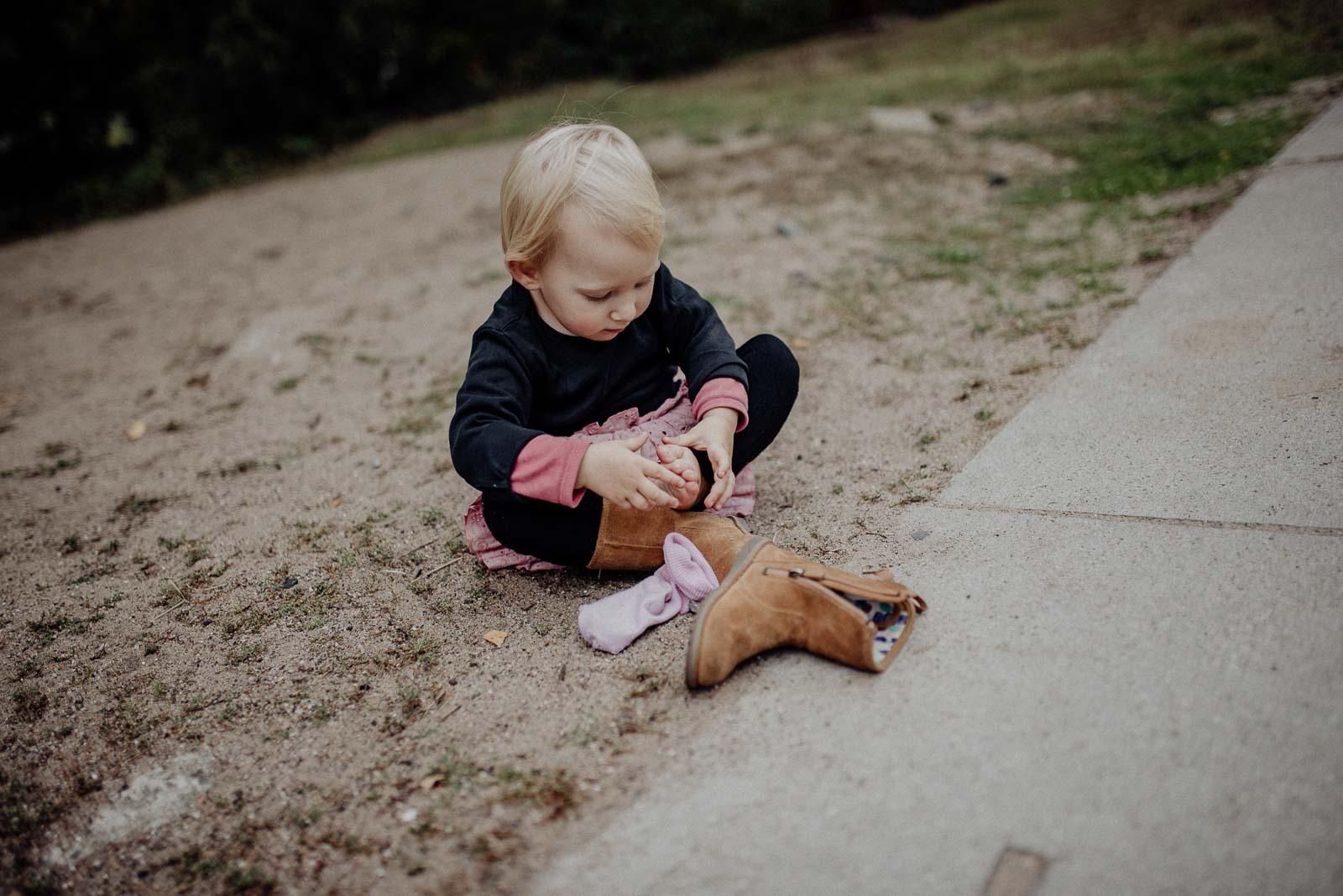 Kleines Mädchen zieht Ihre Stiefel an