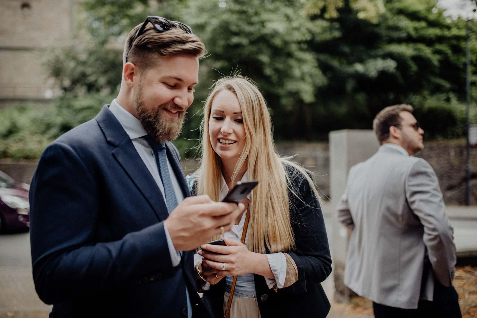 Hochzeitsgaeste checken ihr Handy