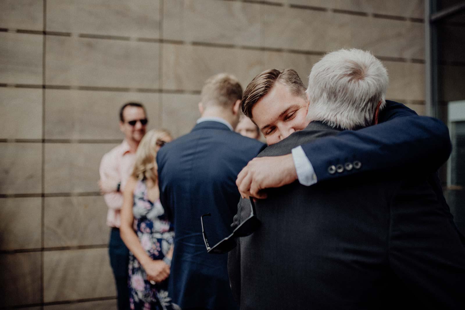 Enkel umarmt Opa bei Hochzeit