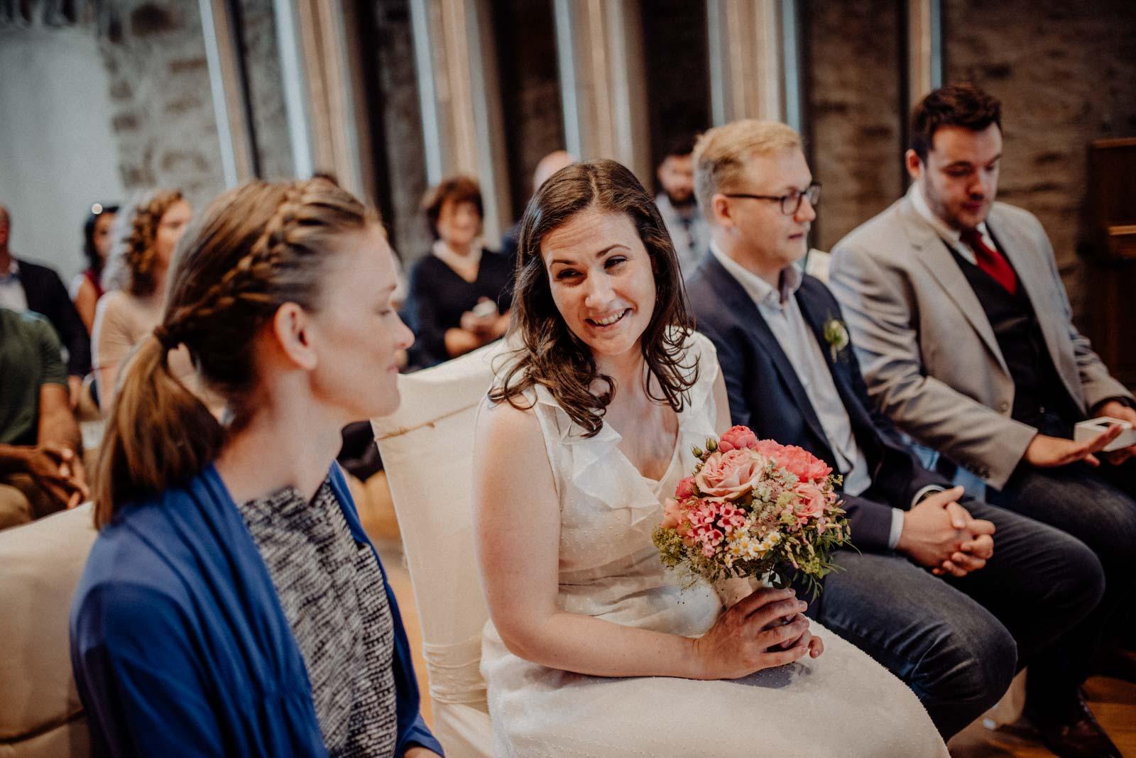 Braut strahlt Trauzeugin im Traumzimmer an