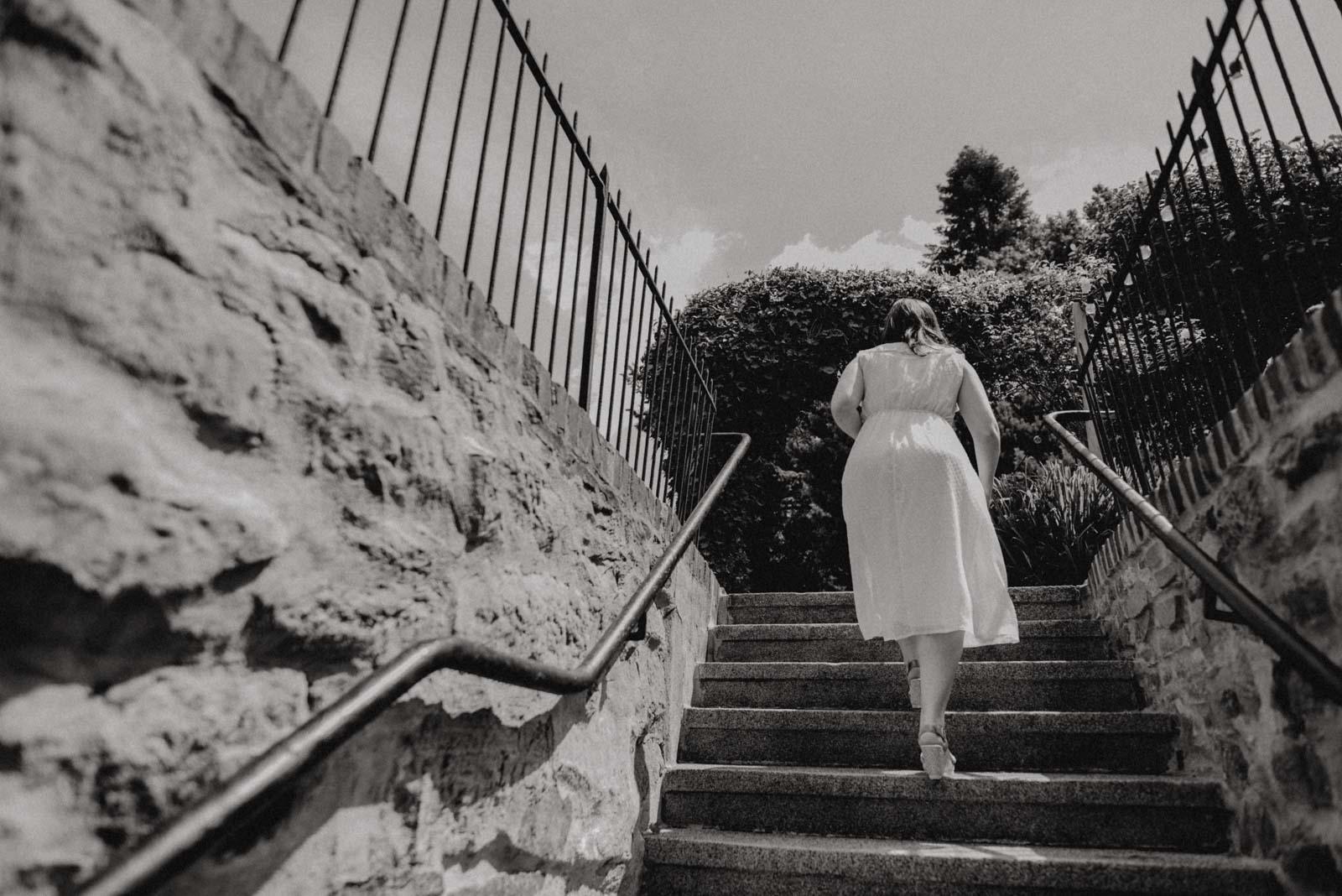 Die Braut geht die Treppe zum Garten hoch