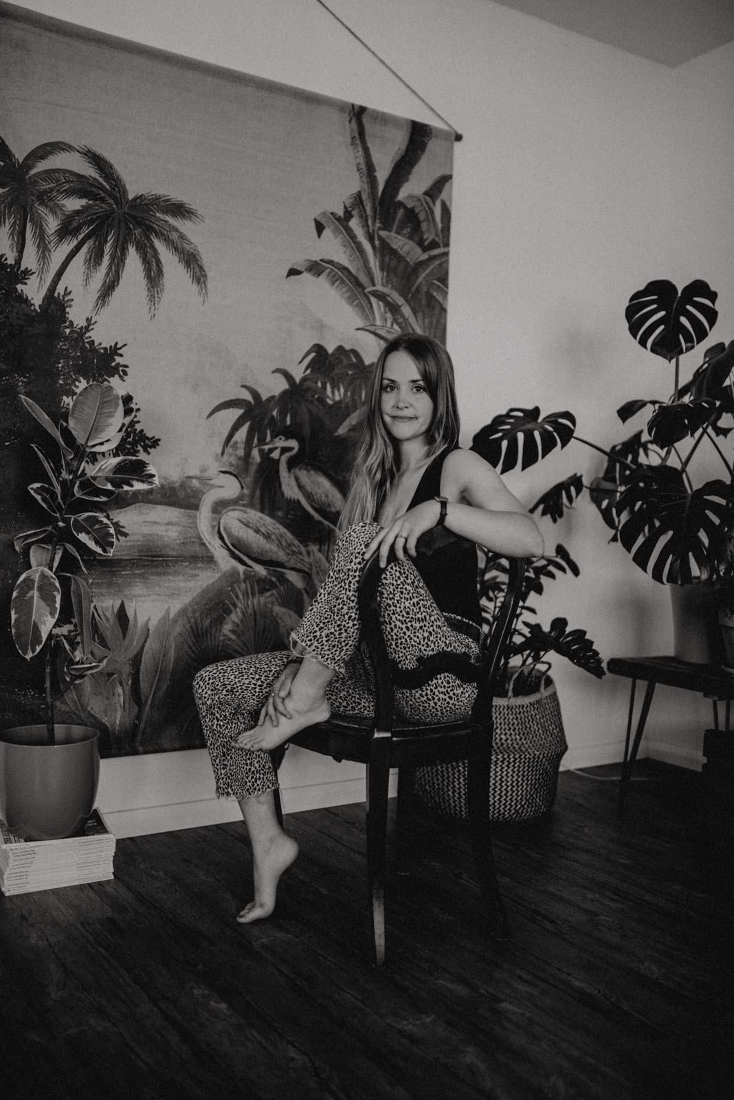 Junge Frau sitzend auf einem Stuhl vor Dschungel Wandbild