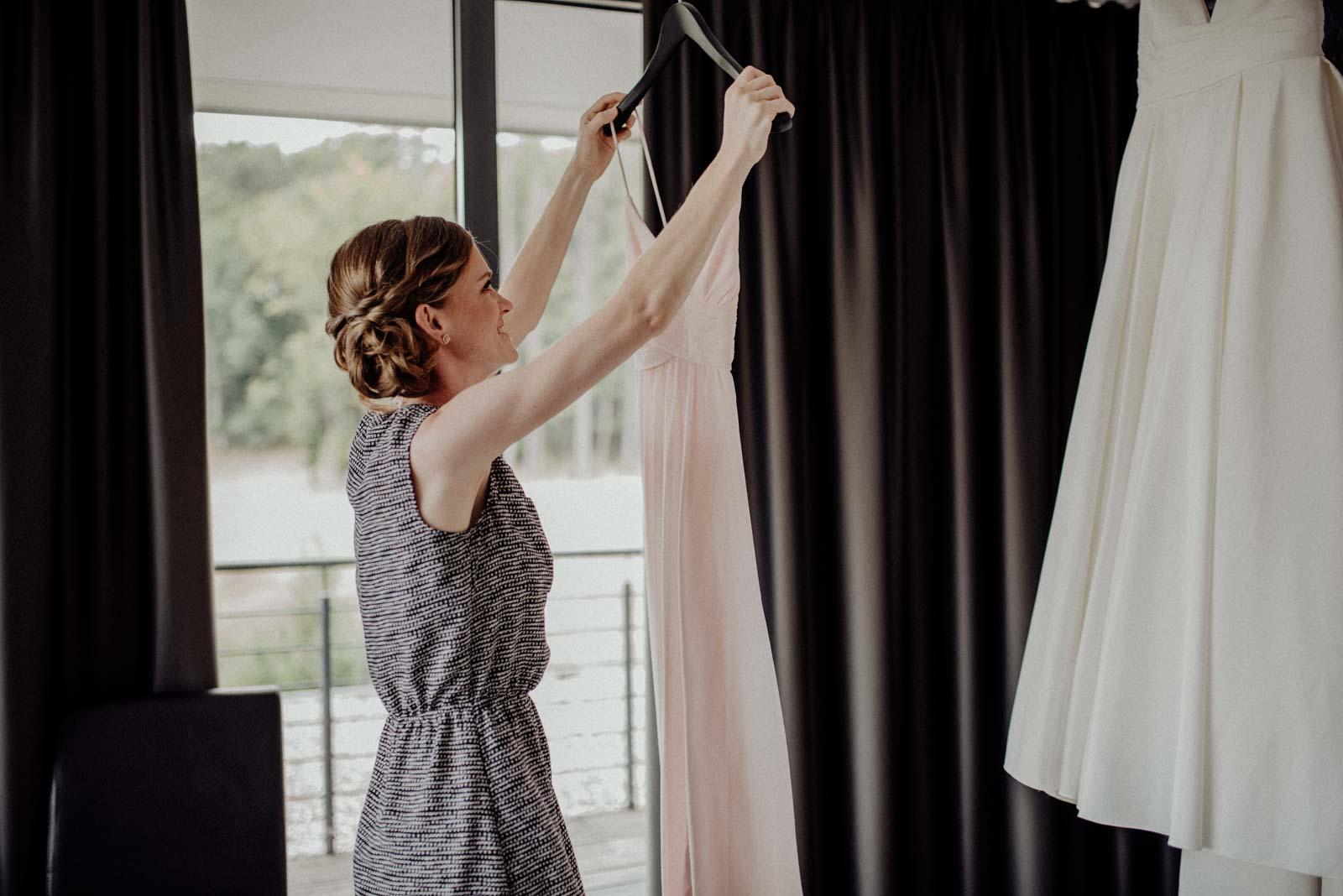Trauzeugin nimmt ihr Kleid vom Buegel