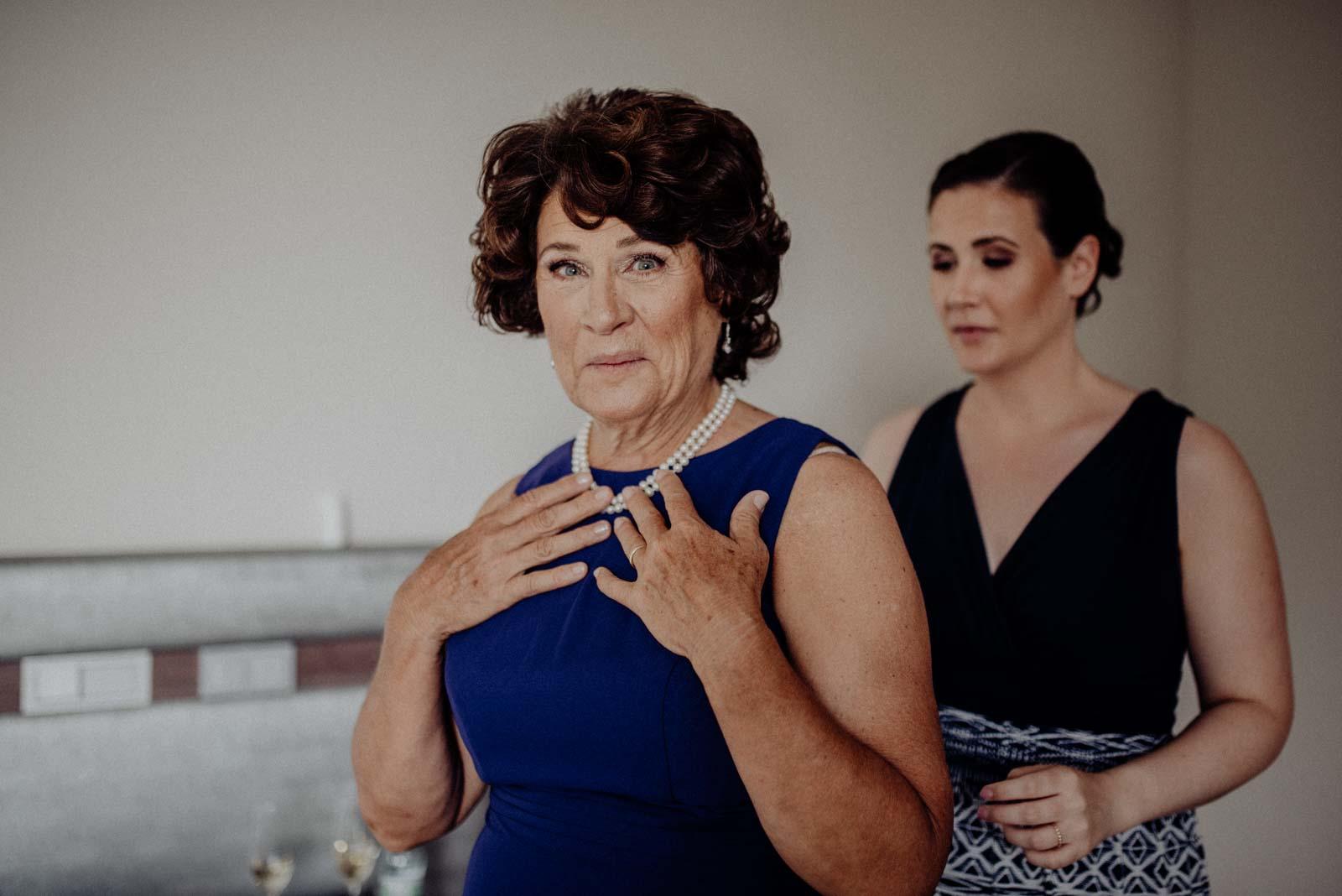 Braut hilft Brautmutter beim Anziehen von kleid und Schmuck
