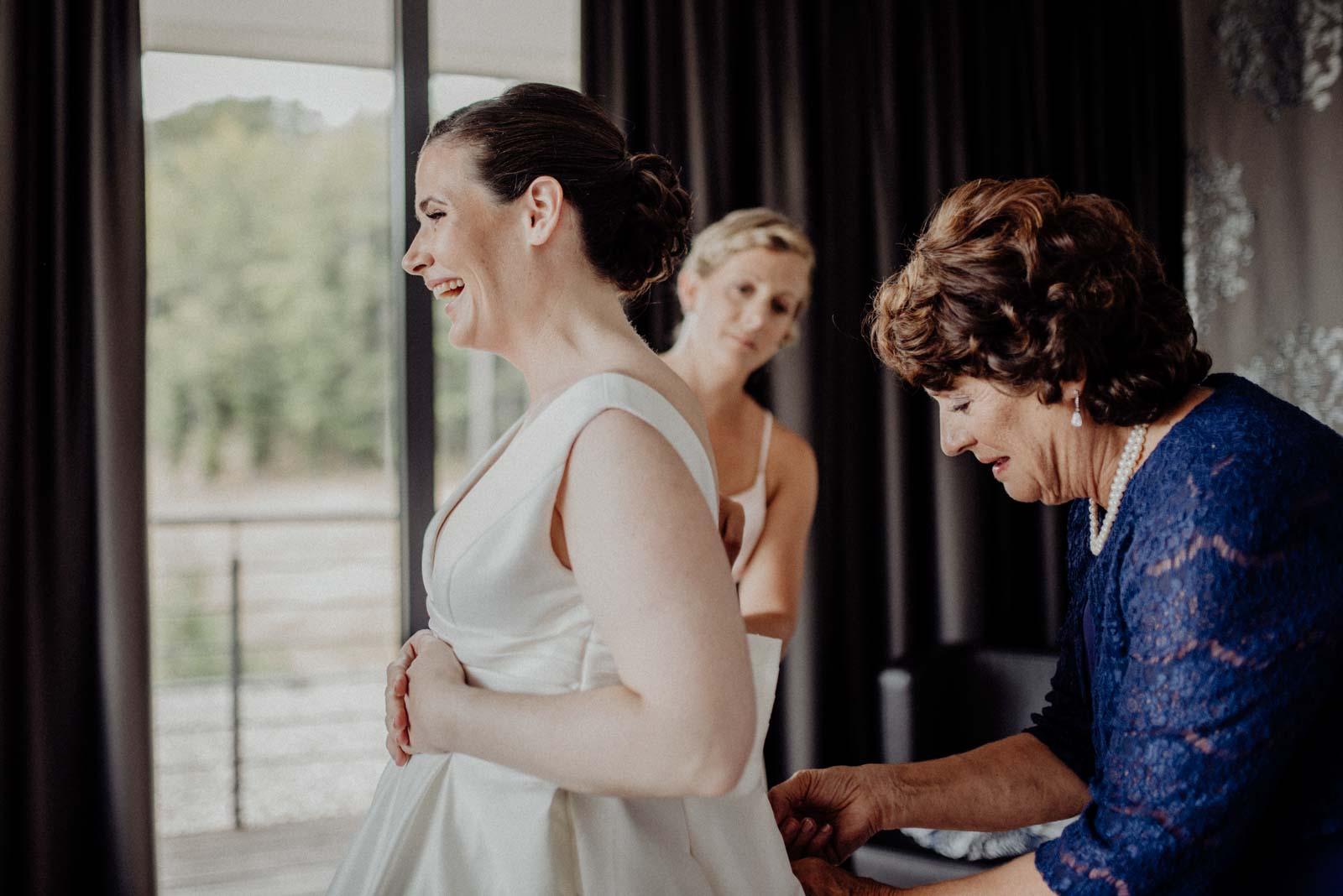Brautmutter hilft ihrer Tochter ins Hochzeitskleid