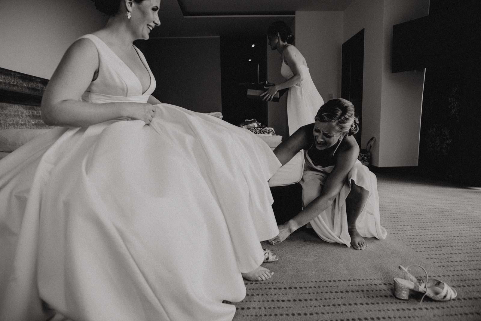 Brautjungfer hilft Braut ins Hochzeitskleid