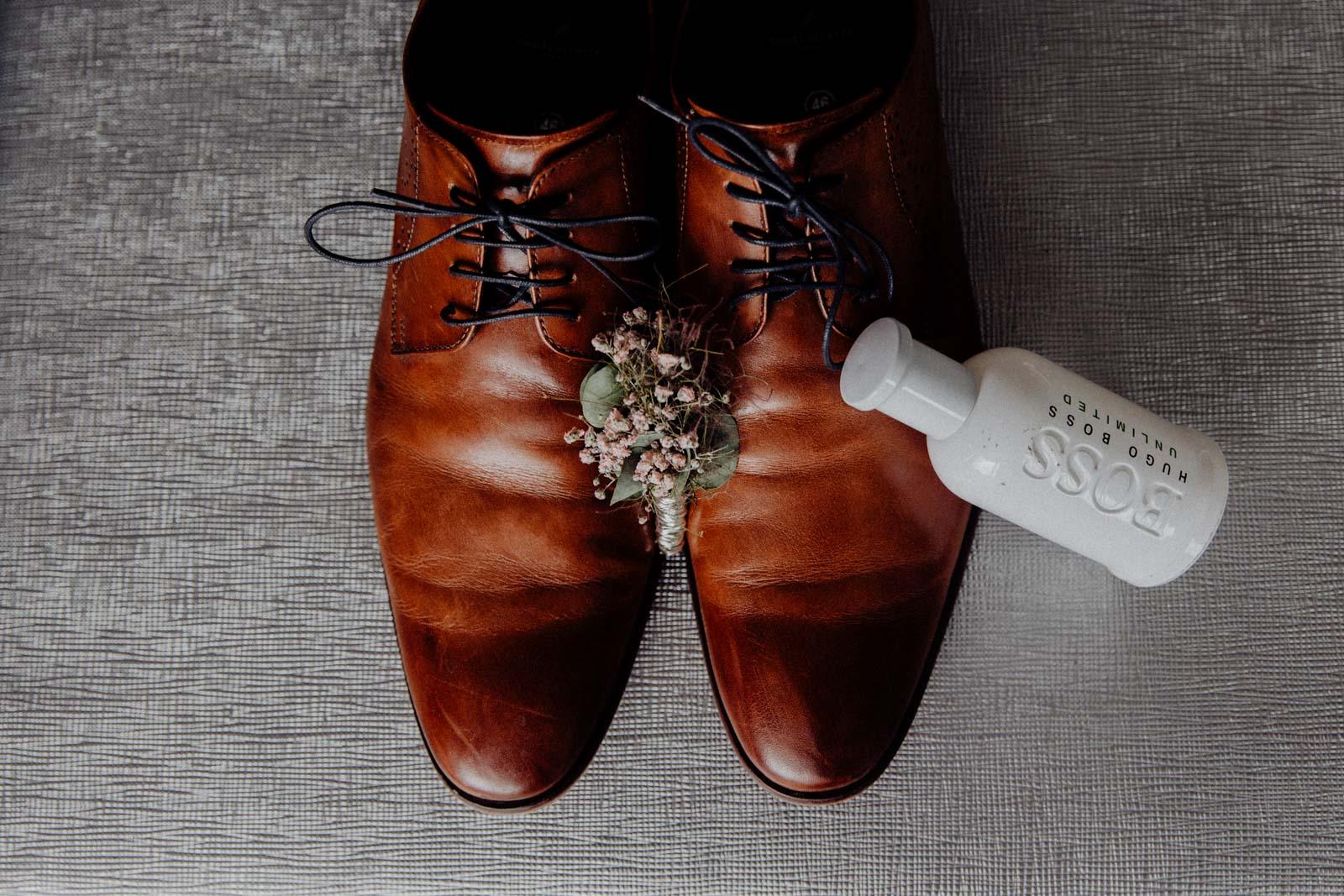 Schuhe des Braeutigams beim Getting Ready mit PArfum und Blumen arrangiert