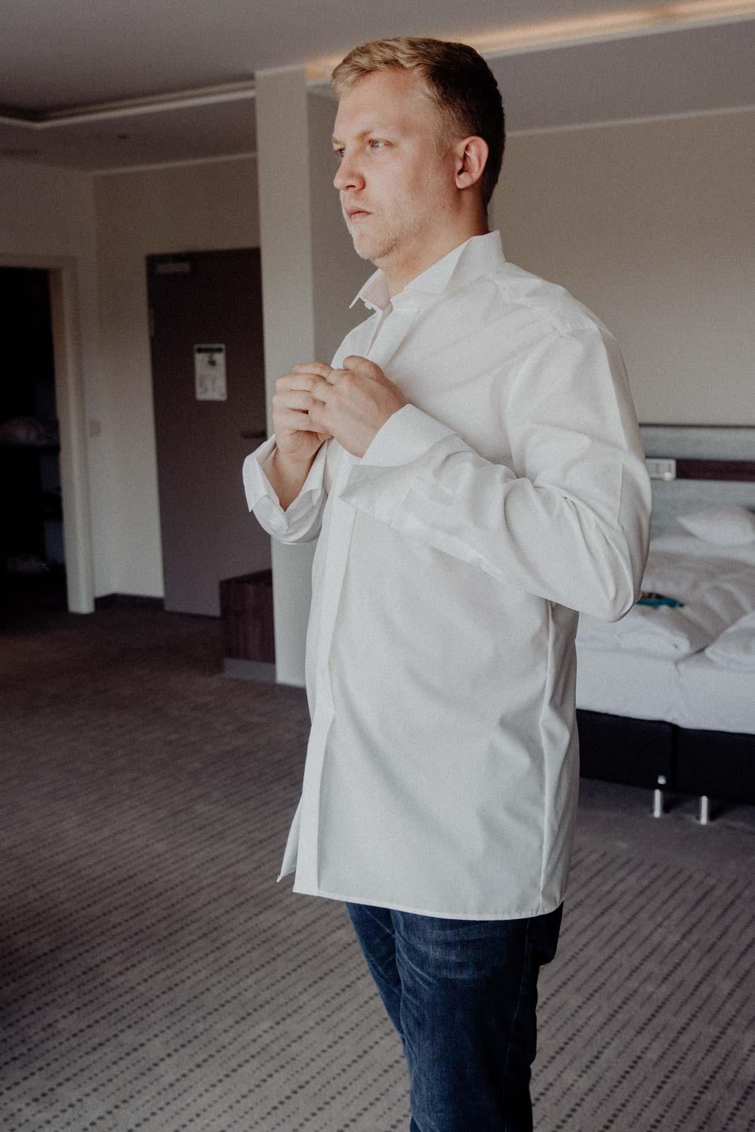 Braeutigam zieht sich im Hotelzimmer an