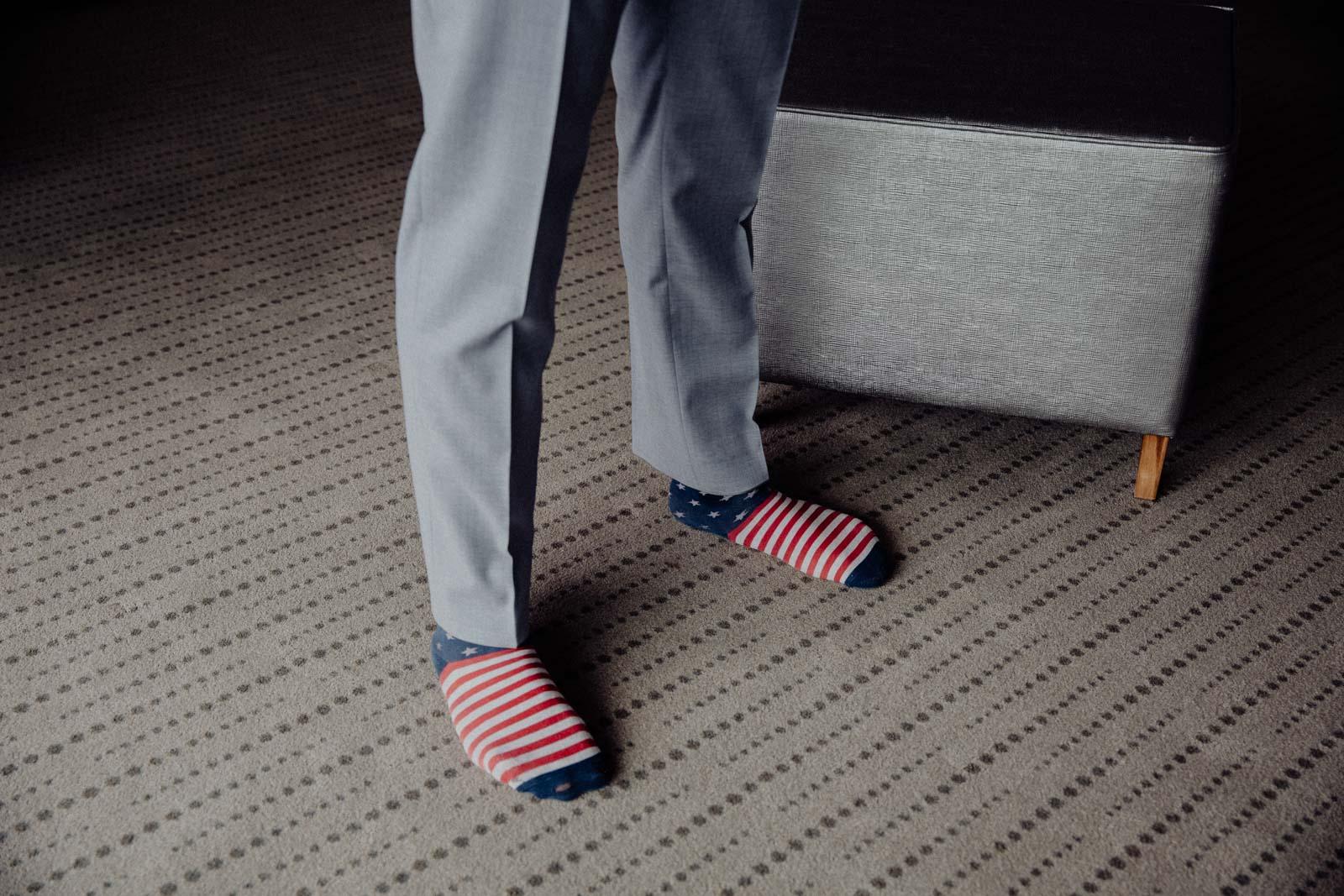 Braeutigam zieht sich im Hotelzimmer an und traegt bunte Socken
