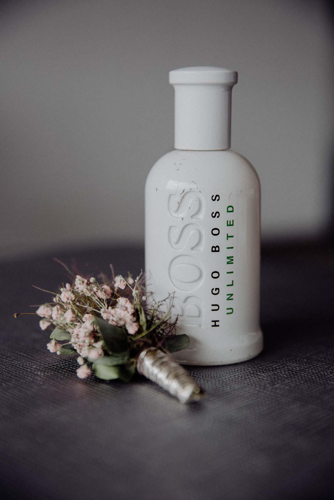 PArfumflasche und Blumenanstecker des Braeutigams