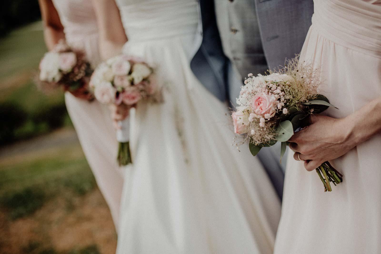 Brautjungfern und Braut zeigen ihre Blumenstraeuße