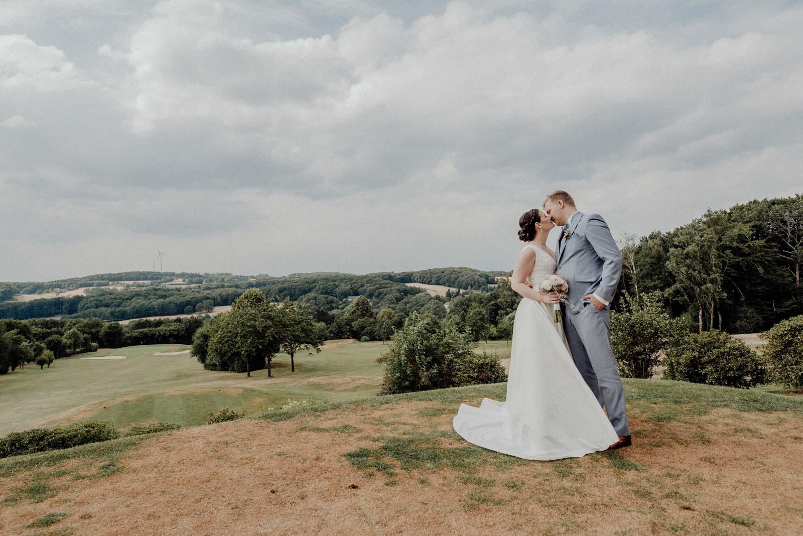 Romantischer Kuss beim Paarshooting auf dem Golfplatz Vesper