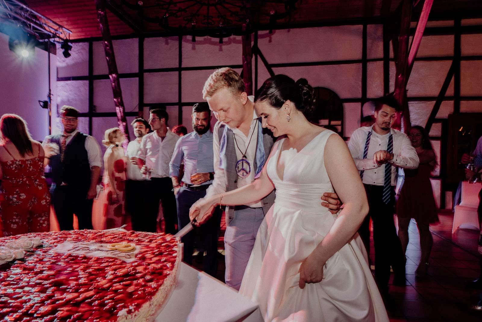 Tortenanschnitt waehrend der Hochzeitsparty