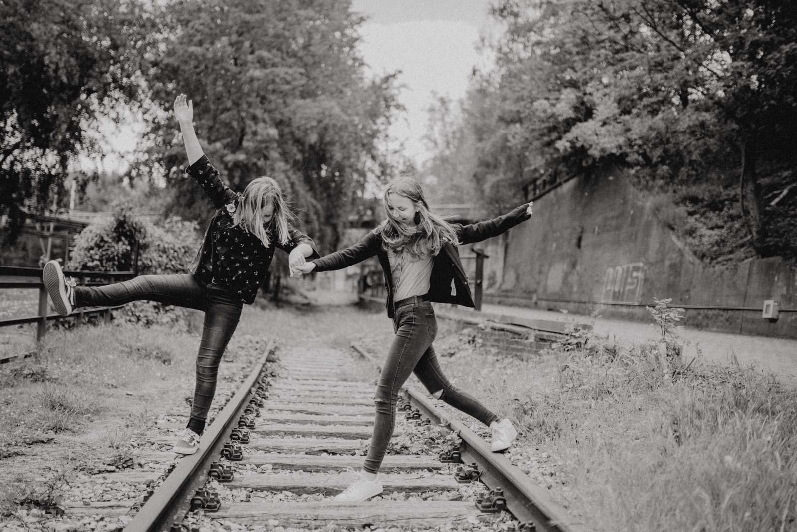 Schwestern toben beim Familienshooting auf stillgelegten Schienen.