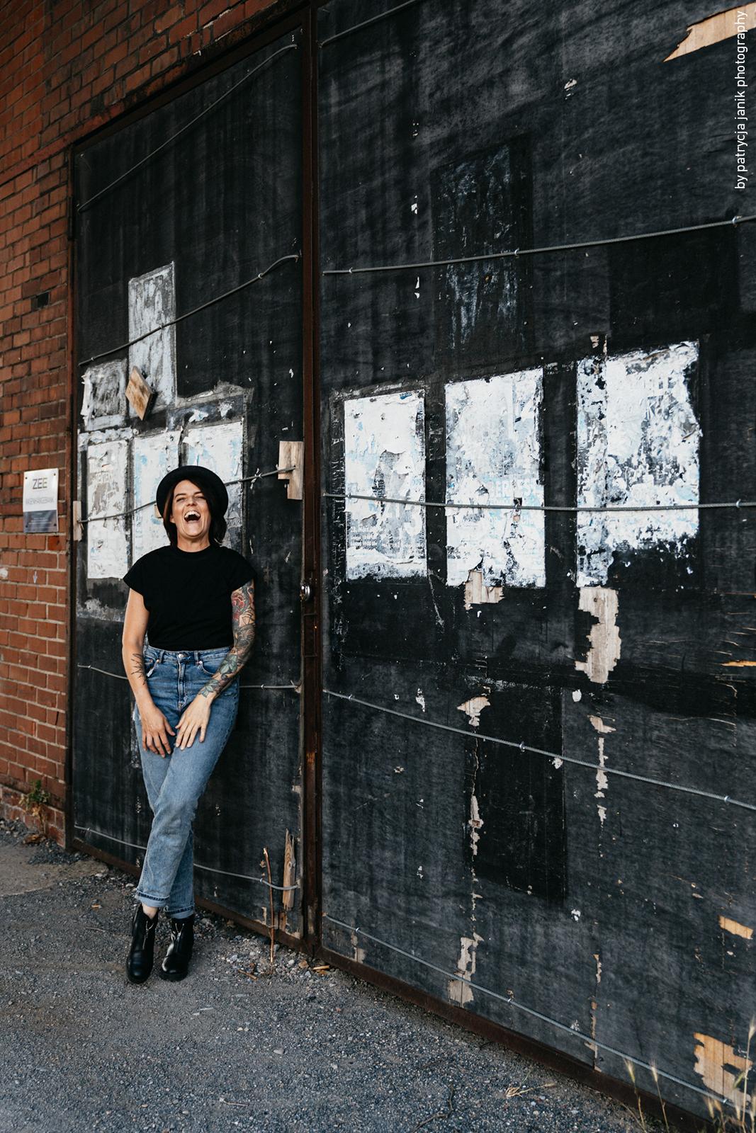 Fotografin mit Hut vor Plakatwand im Industriegebiet
