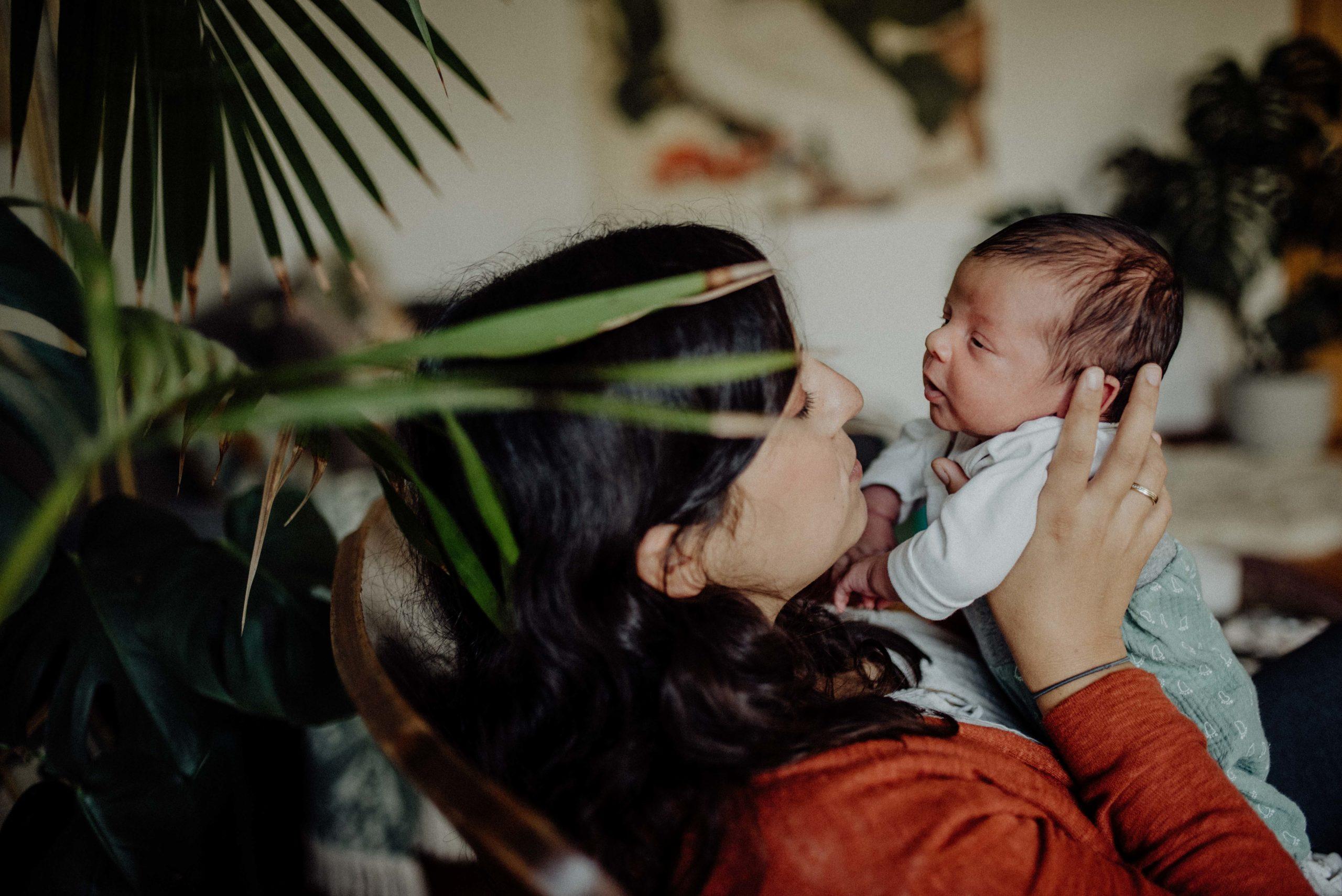 Mama und Baby im Schaukelstuhl sehen sich an.