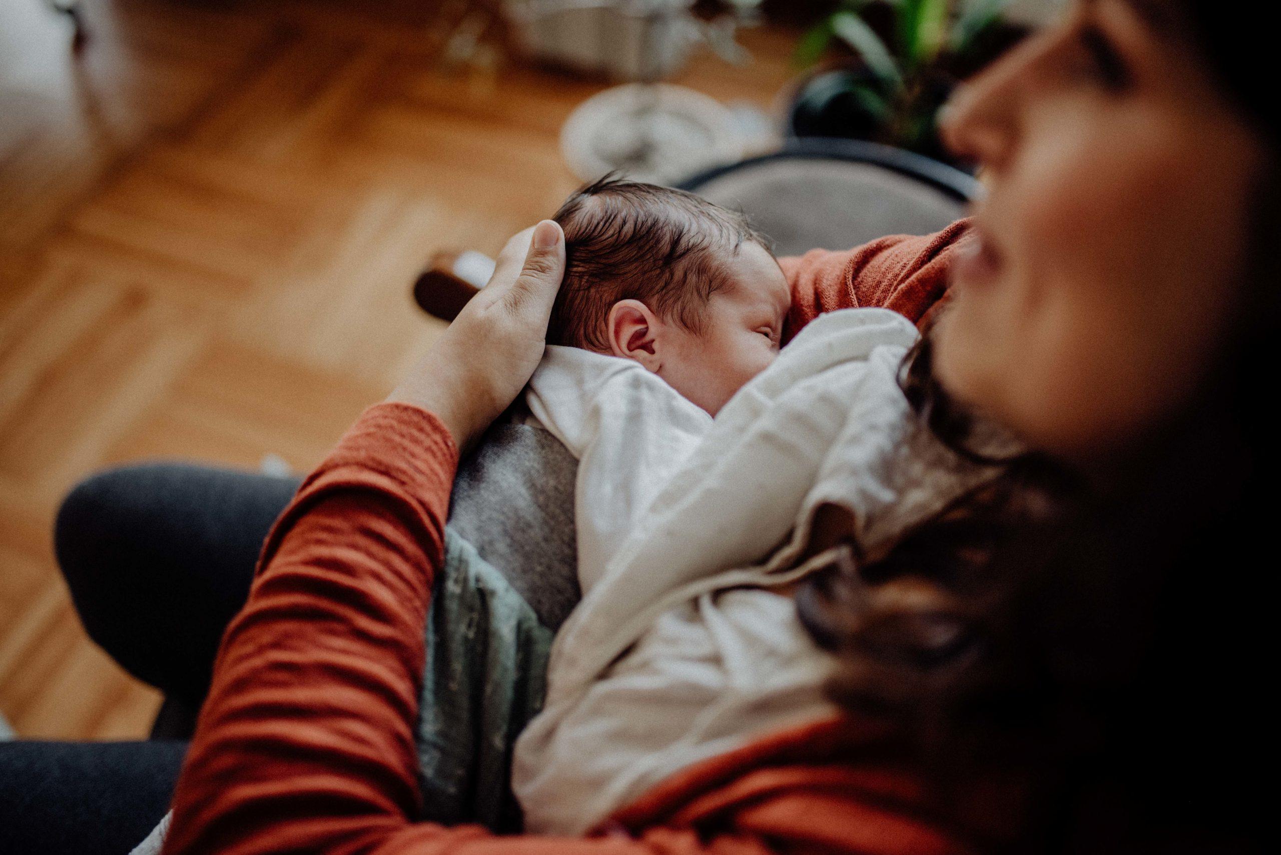 Zwei Wochen altes Baby wird gestillt.