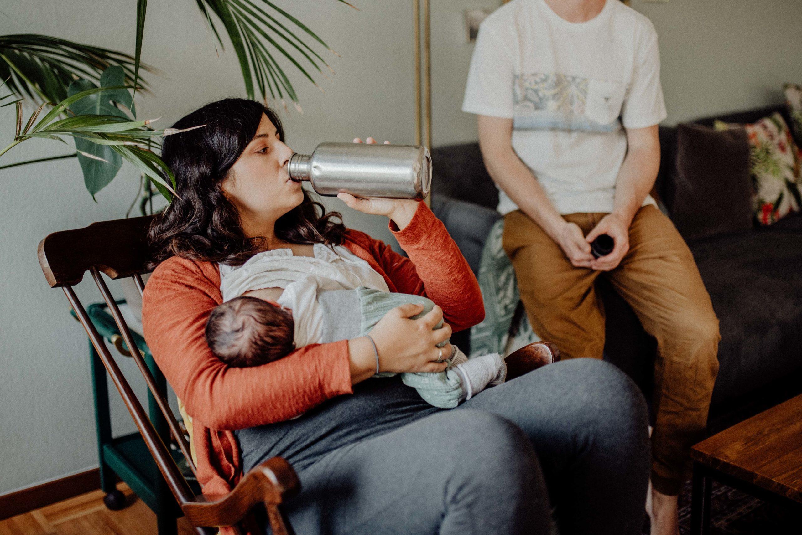 Mutter trinkt aus Feldflasche während Sie Ihr Baby stillt.