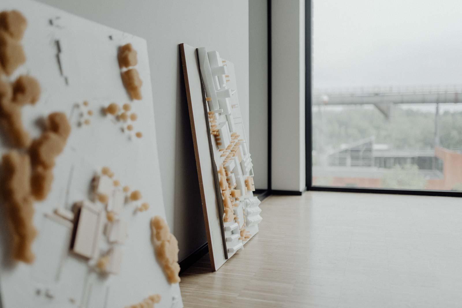 Architekturmodelle lehnen laessig an der Wand im Buero