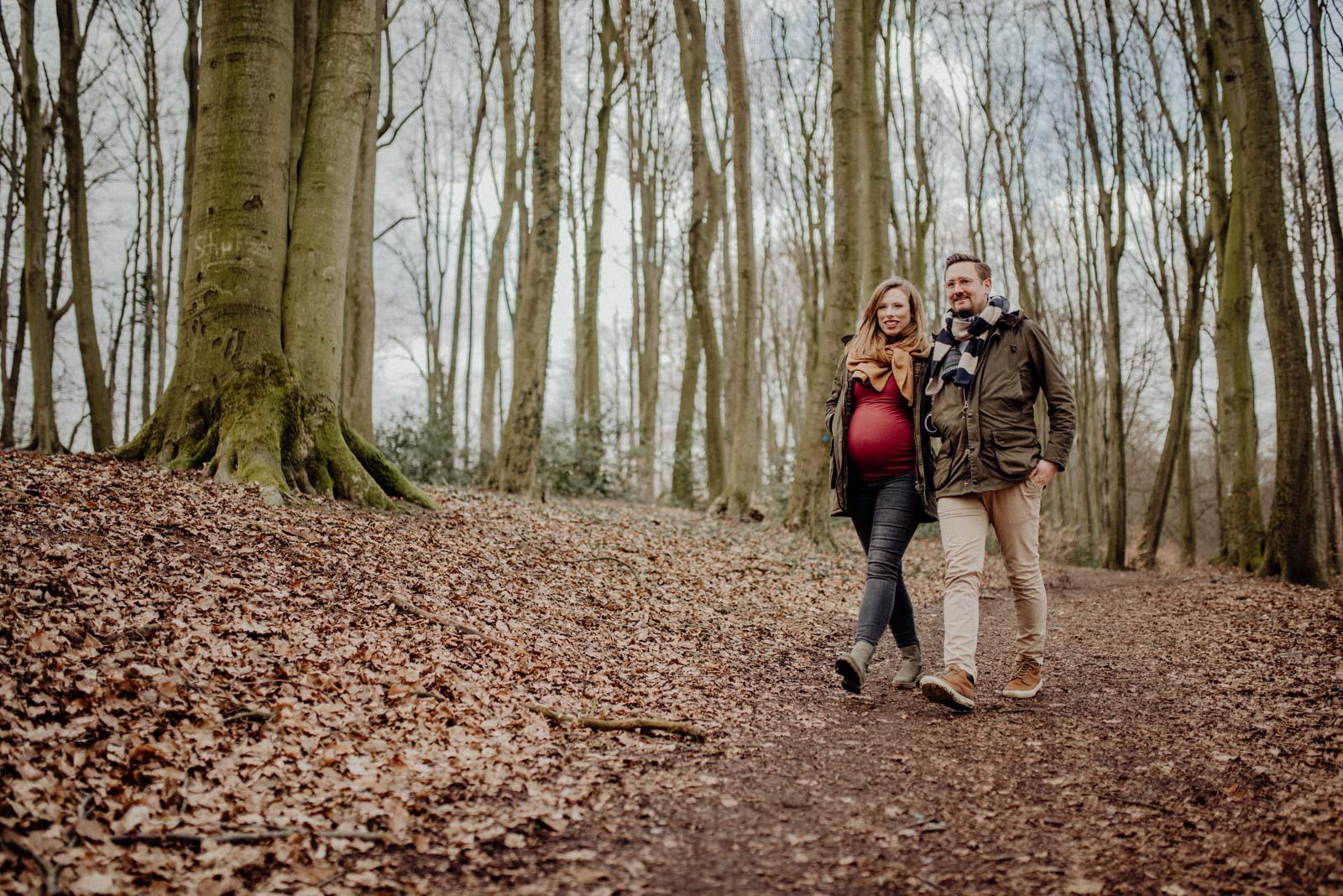 Pärchen mit babybauch geht im Wald spazieren