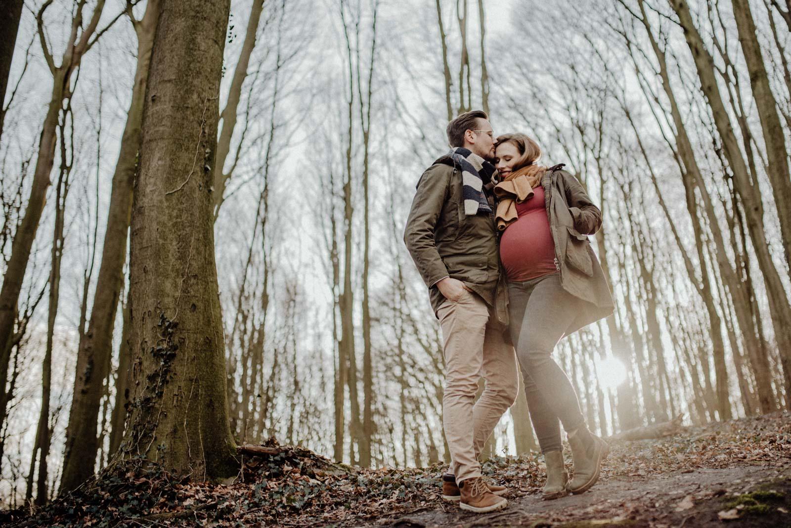 Pärchen im Wald bei Sonnenuntergang mit Babybauch