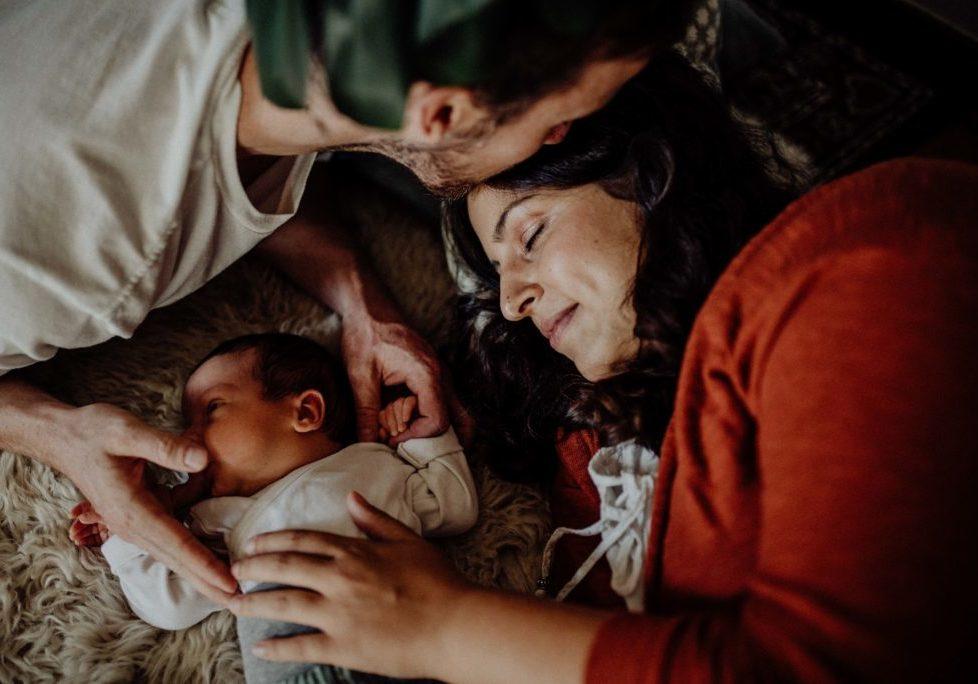 Familie liegt mit Neugeborenem Baby auf Schaffell im Wohnzimmer